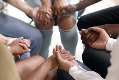 Teilnehmer einer Gruppentherapie halten sich an den Händen und bilden einen Kreis