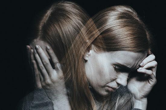 Junge Frau leidet unter Traumafolgestörungen und hält sich die Hände vor das Gesicht
